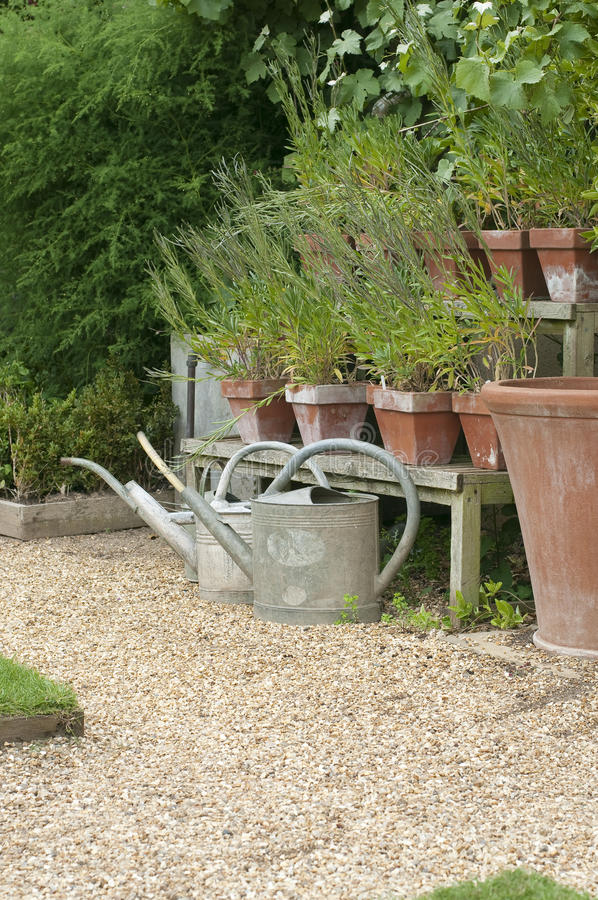 English cottage garden. Watering cans and flower pots in English cottage garden stock photo