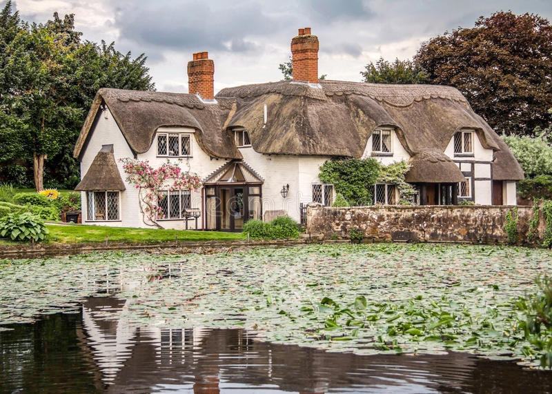 English Cottage with Pond in Badger, Shropshire. An English country cottage, complete with Roses and a pond which reflects the cottage royalty free stock photo