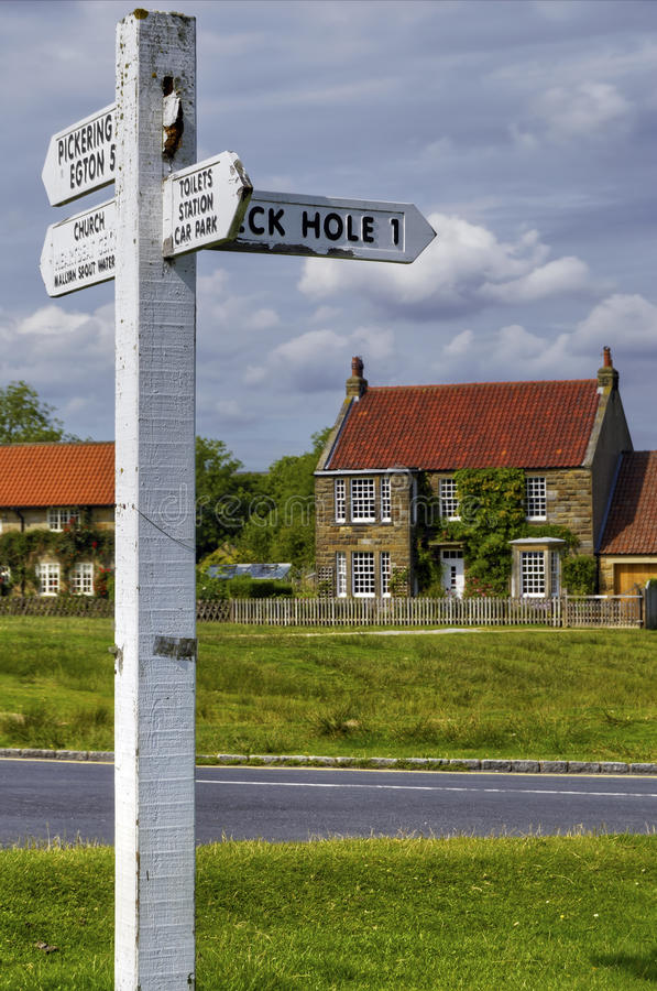 English cottage and street. Signpost in the English village of North Yorkshire with a cottage in the background stock photos