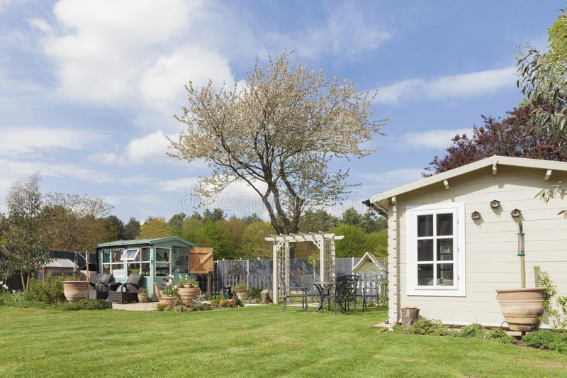 English country garden with summerhouse. English garden in rural East Anglia in Norfolk. Large outside private garden with trees potting shed and summerhouse royalty free stock photography