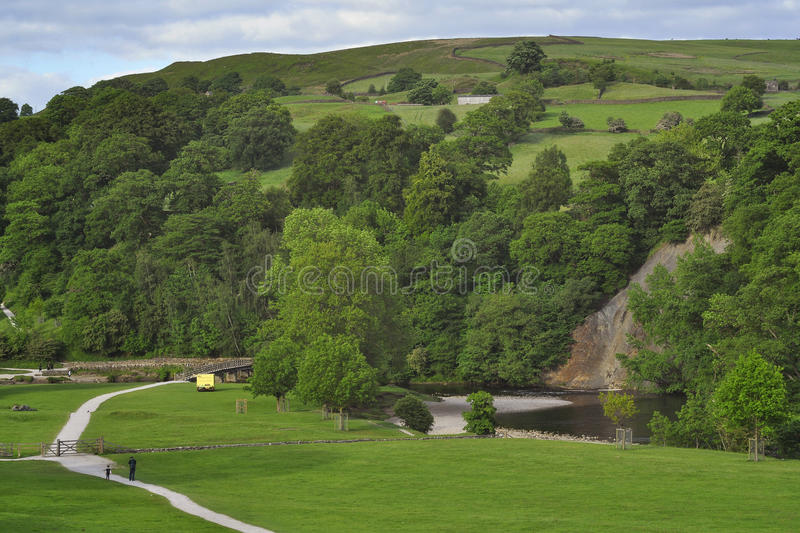 English countryside landscape: hills, trees, path. English countryside landscape around Bolton Abbey, Yorkshire Dales, with footpath in grassy meadow, trees royalty free stock images