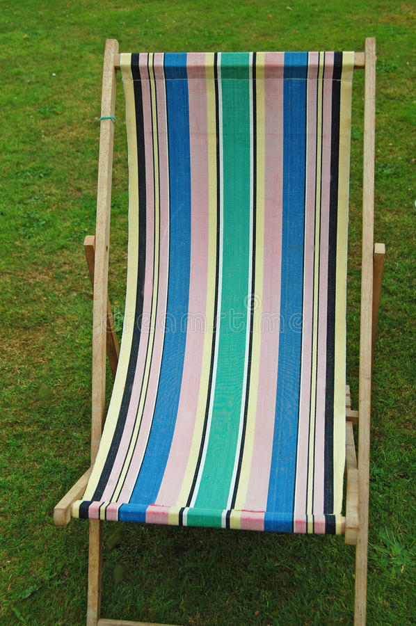 English deckchair. Old english vintage striped deckchair in garden royalty free stock photo
