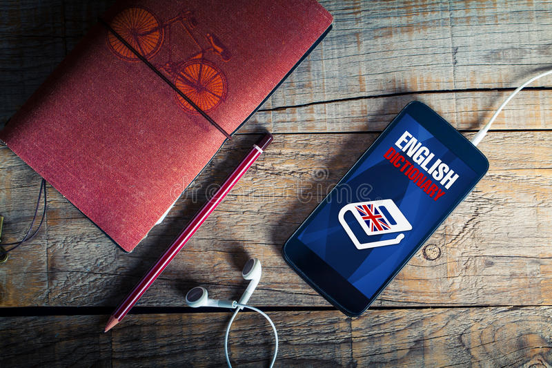English dictionary app in a mobile phone. Top view of mobile, pencil, notebook and earphones, with english dictionary application on mobile screen stock image