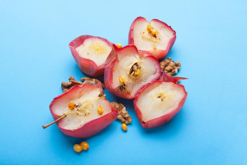 English dietary breakfast - baked apples with nuts and berries on a blue background royalty free stock photos
