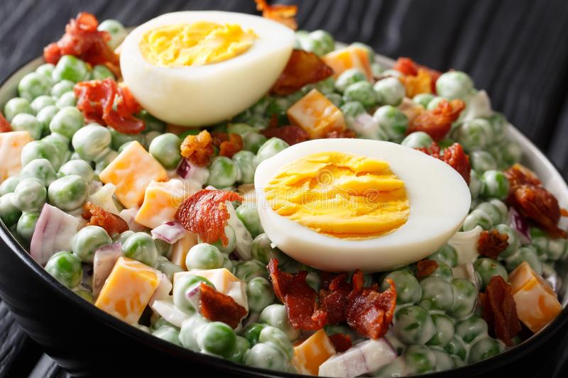 English Easter salad with fresh green peas, boiled eggs, bacon and cheddar cheese with sauce close-up in a bowl on the table. royalty free stock images