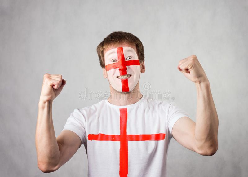English fan with painted face and t-shirt rejoices. White man. Studio shooting royalty free stock photography