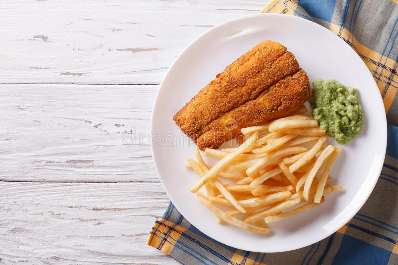 English food: fried fish in batter with chips. horizontal top vi. English food: fried fish in batter with chips and pea puree on a plate. horizontal view from stock photos
