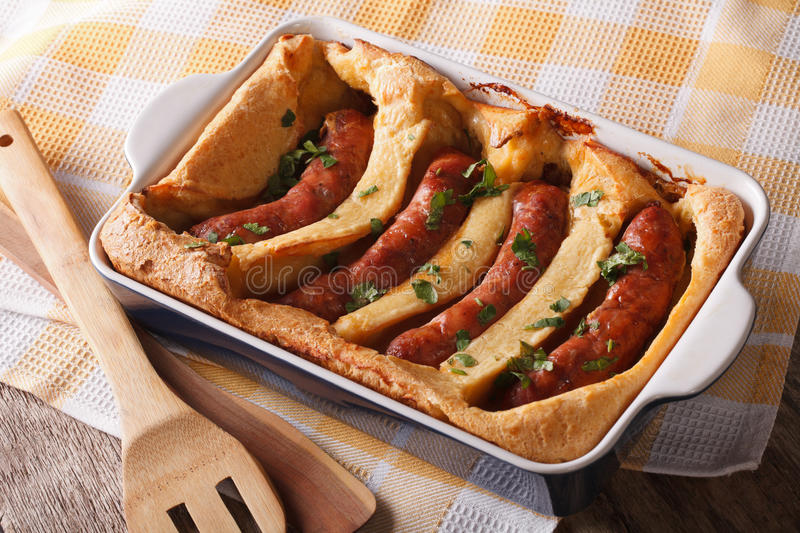 English food: toad in the hole into a baking dish close up. Horizontal. English food: toad in the hole into a baking dish close up on the table. Horizontal stock photography