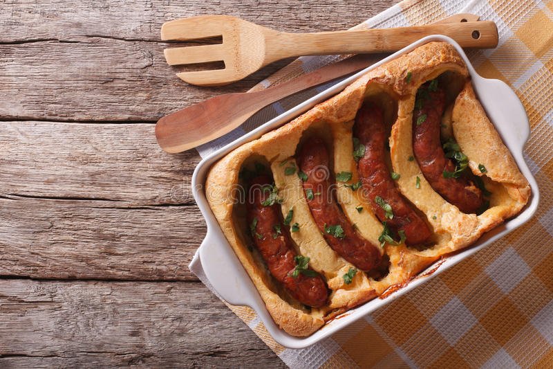 English food: toad in the hole into a baking dish. horizontal to. English food: toad in the hole into a baking dish on the table. Horizontal top view royalty free stock photos