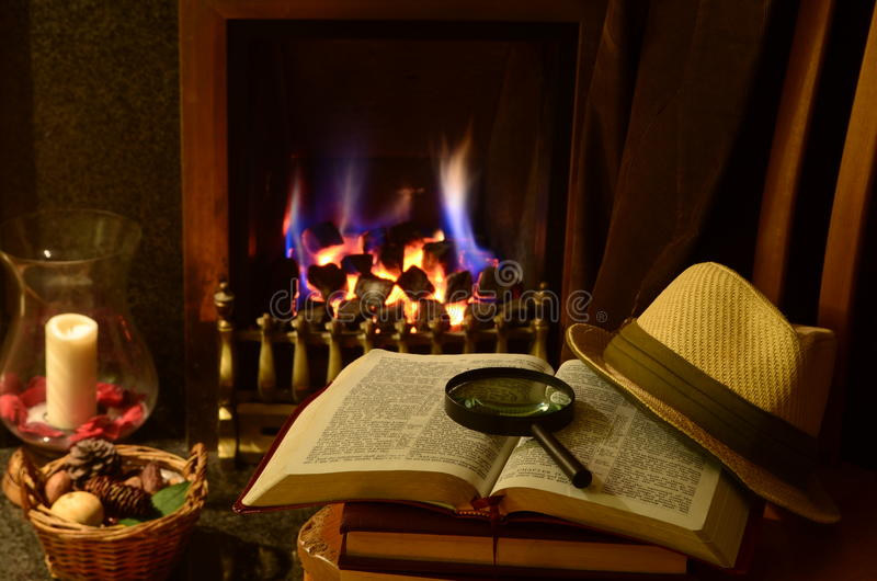 English gentlemans study. English gentlemans hat with books in front of roaring log cabin fire stock photography