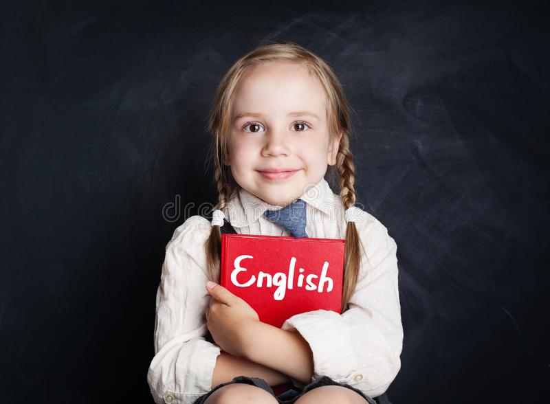 English language concept. Cute child pupil with book smiling royalty free stock image