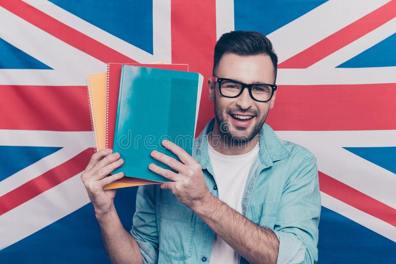English language learning concept-portrait of cheerful attractive man with bristle showing colorful copy books standing over Engli. Sh flag background stock photo