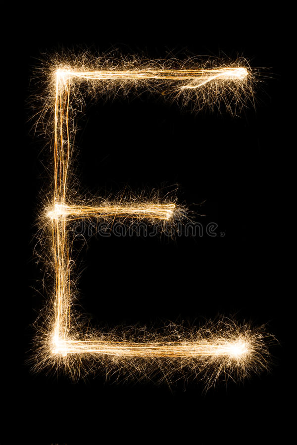 English Letter E from sparklers alphabet on black background. English big Letter E made from burning sparkles on black background. Shiny festive party firework stock photos