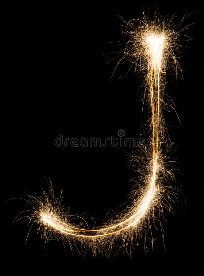 English Letter J from sparklers alphabet on black background. royalty free stock image