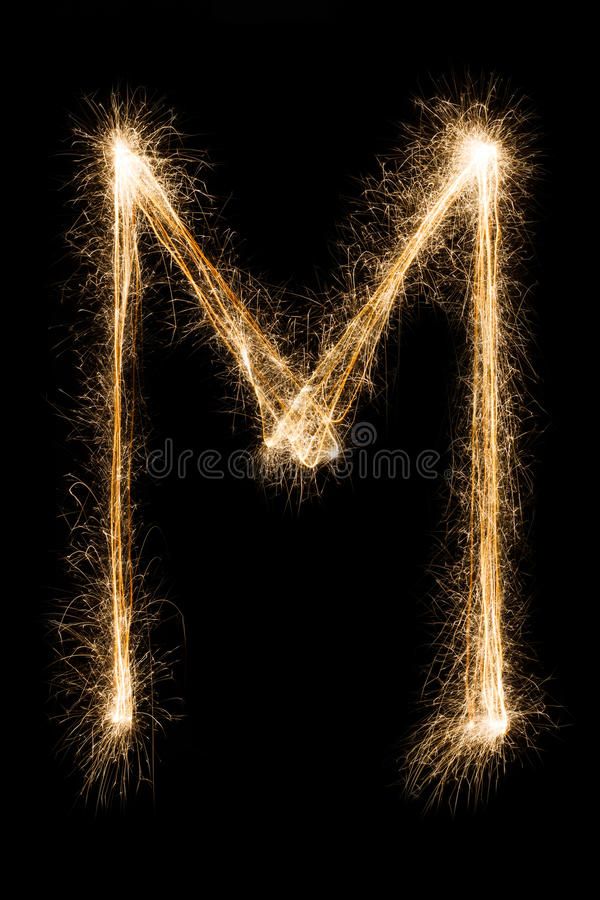 English Letter M from sparklers alphabet on black background. English big Letter M made from burning sparkles on black background. Shiny festive party firework royalty free stock photos
