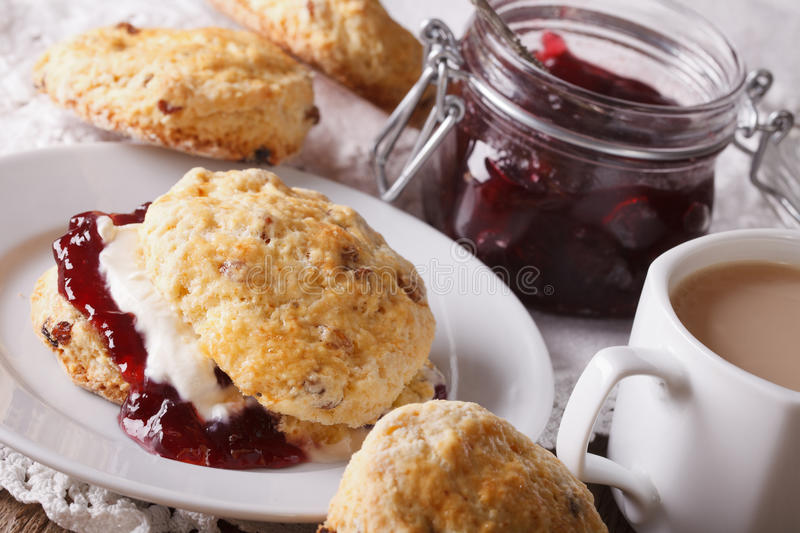 English pastries: scones with jam and tea with milk close-up. Ho royalty free stock image