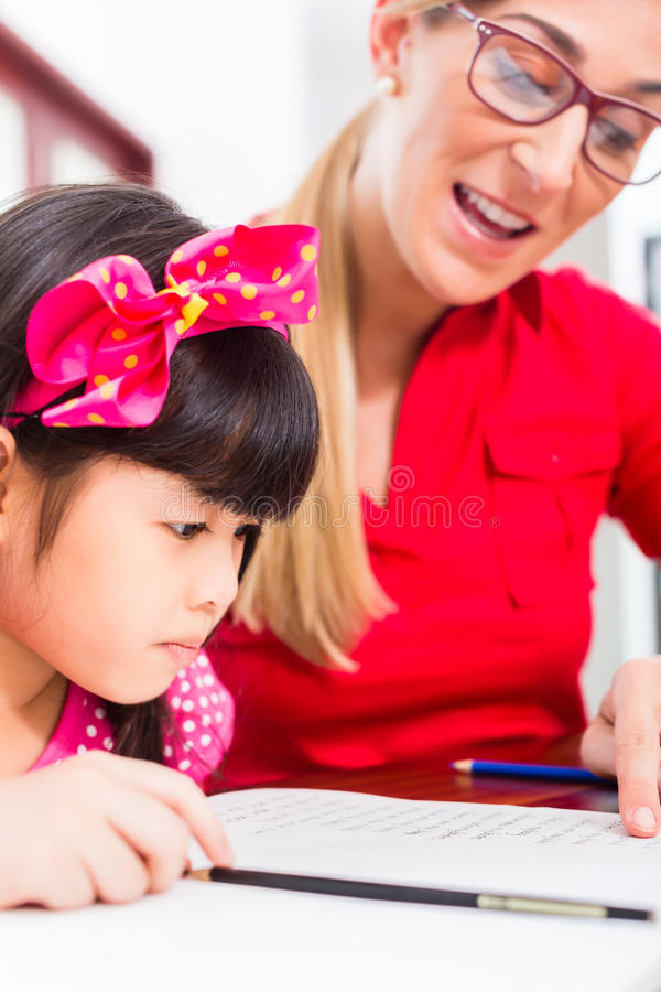 English private teacher working with Asian girl. English private teacher helping Asian girl with homework stock image