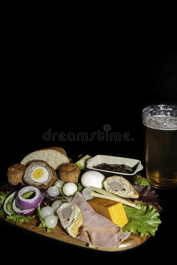 English pub food. Traditional English pub meal of a ploughman's lunch served with a pint of lager. The typical cold food includes pork pies, ham, hard stock photo