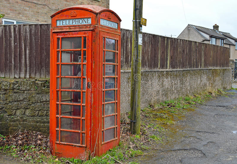 An English Red Phone Box. An old looking phone box on a street corner royalty free stock photography
