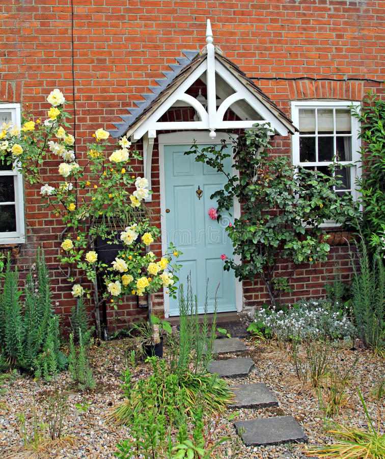 English rose country cottage. Photo of a pretty english country cottage surrounded by sweet scented roses stock image
