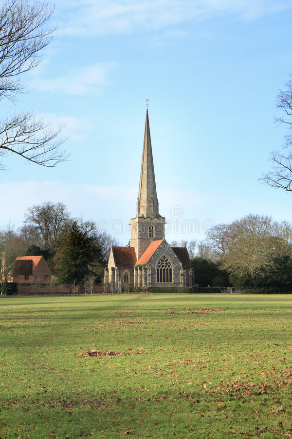 English Rural Church. Medieval English Rural Church with a tall Steeple against a Blue Winter sky royalty free stock photography