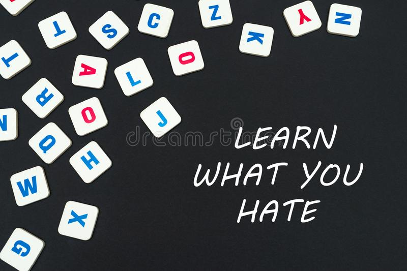 English colored square letters scattered on black background with text learn what you hate. English school concept, text learn what you hate, colored square stock photos
