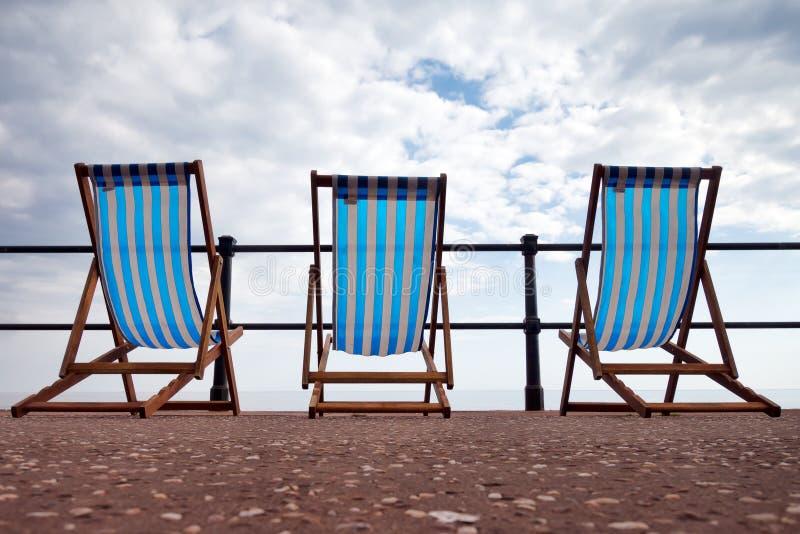 English seaside summer, bad weather. Deserted deckchairs,nobody. stock image