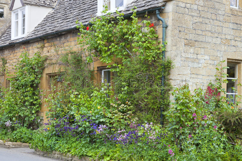 English stone house with colourful cottage front garden. Front of English limestone cottage with colorful, flowering garden royalty free stock photos
