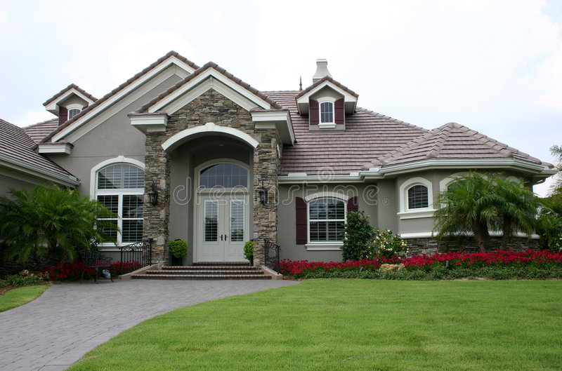 English style estate home. Beautiful gray and white English style estate home with tropical landscaping, gabled roof, arched windows and white trim, bordered by