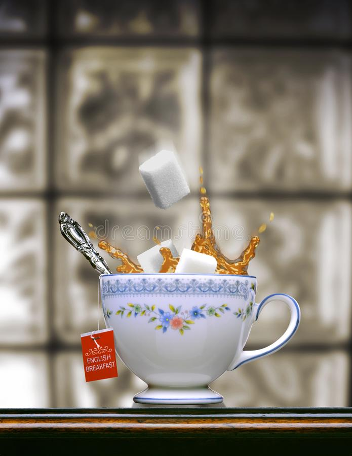 ENGLISH TEA SPLASH WITH WHITE SUGAR CUBES DROPPING ON TABLETOP STILL LIFE stock images