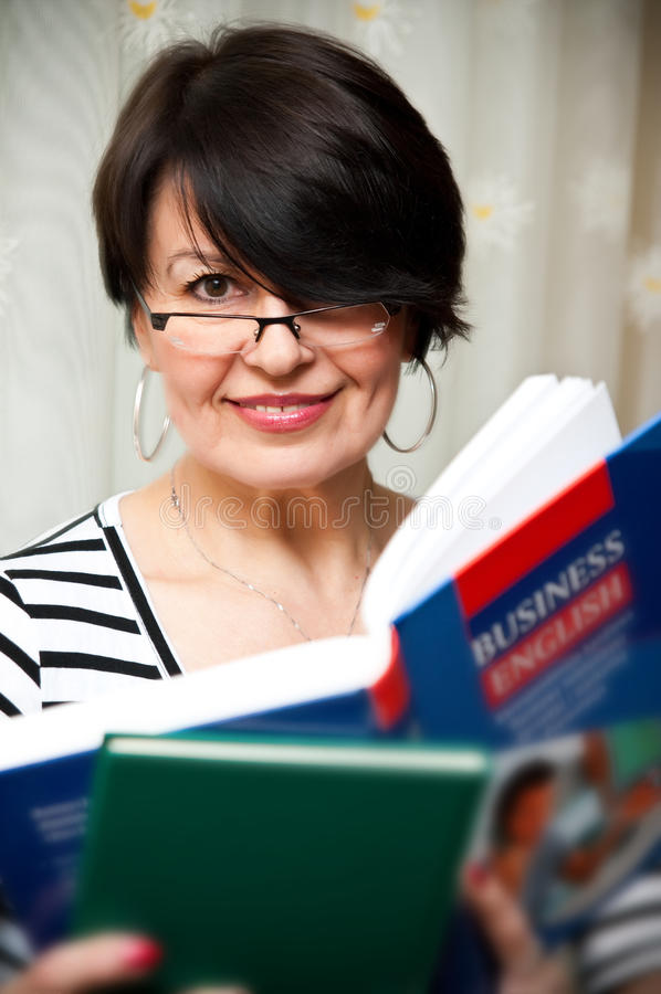 English teacher. Portrait of a female English teacher or adult student holding business english book