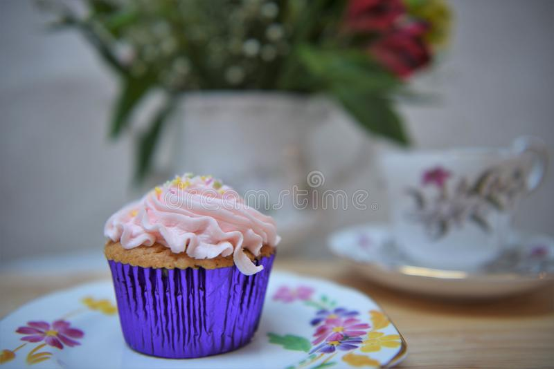 Afternoon tea with vintage floral crockery and a cupcake stock image