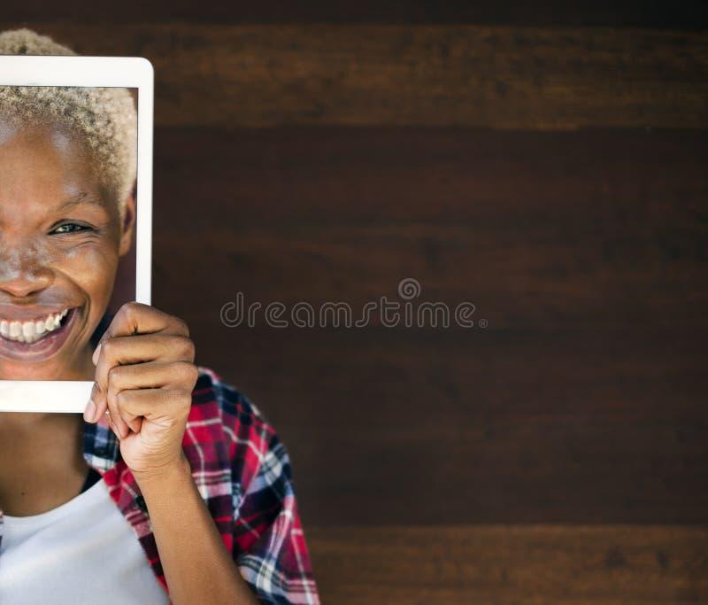 Engodo de sorriso coberto da tecnologia da tabuleta de Digitas da mulher cara africana fotos de stock