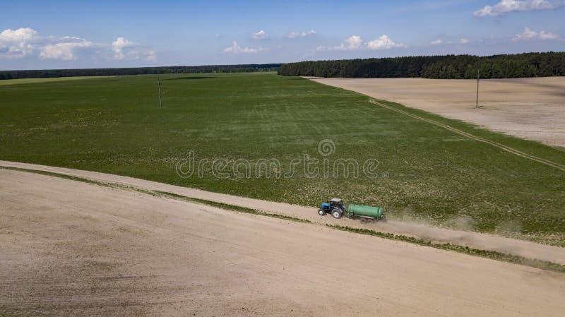 Engrais organique conduit par tracteur sur le champ photos stock