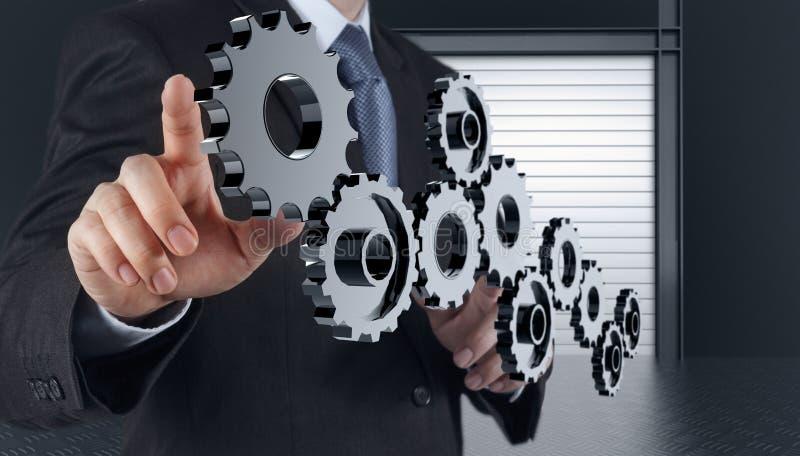 Engranaje de la demostración de la mano del hombre de negocios al éxito foto de archivo