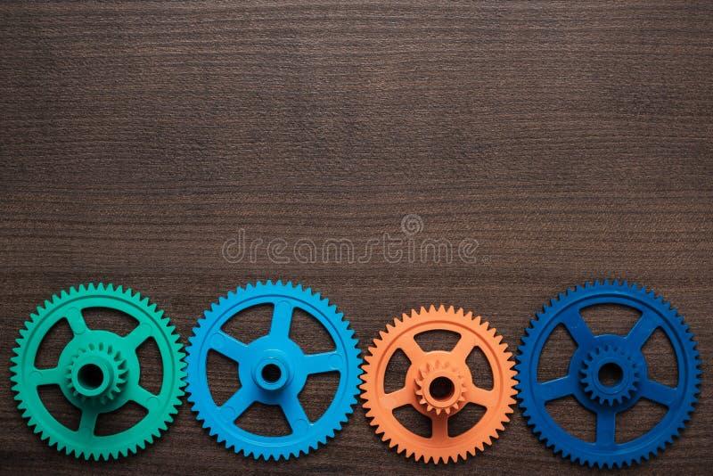 Engranajes coloridos en el fondo de madera foto de archivo libre de regalías