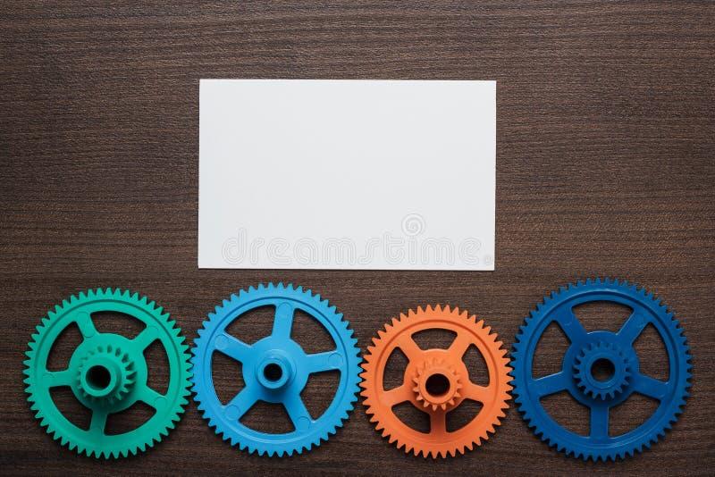 Engranajes coloridos en el fondo de madera marrón imagen de archivo