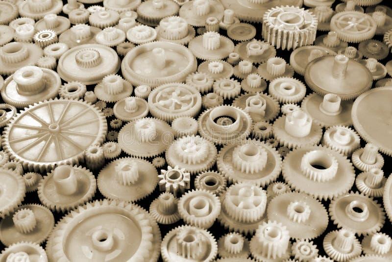 Engranajes y ruedas dentadas plásticos blancos en fondo negro foto de archivo
