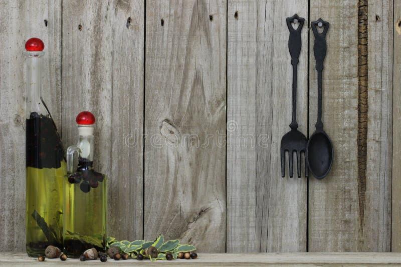 Engrase los tarros de la especia con la cuchara y la bifurcación del arrabio contra el fondo de madera foto de archivo