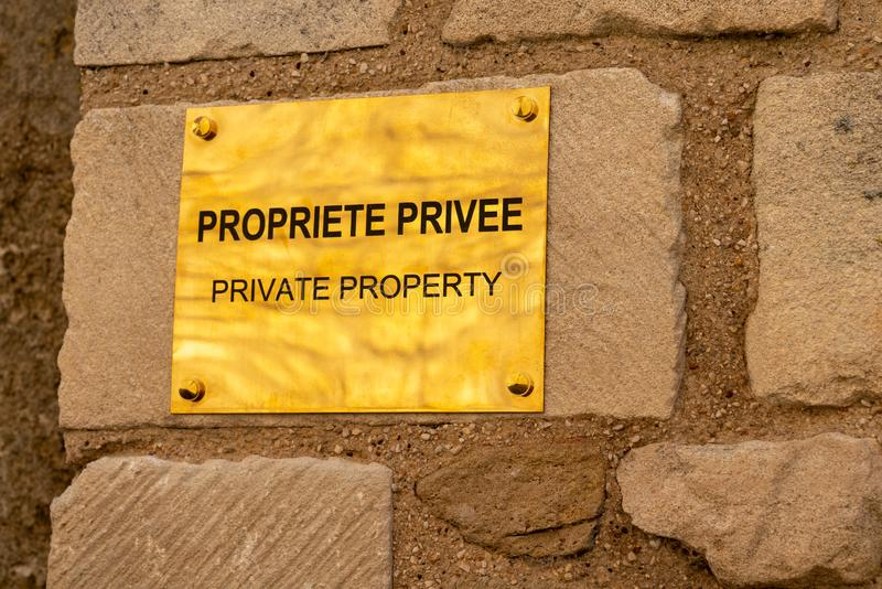 Engraved Private Property Metall Door Plate write in english and French. An Engraved Private Property Metall Door Plate write in english and French royalty free stock image