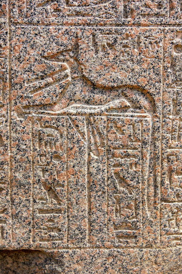 An engraved relief of the canine god Anubis in Memphis in Egypt. An engraved relief of the canine god Anubis (the god of funerals and death) with hieroglyphs on royalty free stock photography