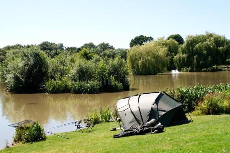 Engrenagem & barraca de pesca ao lado do lago fotografia de stock