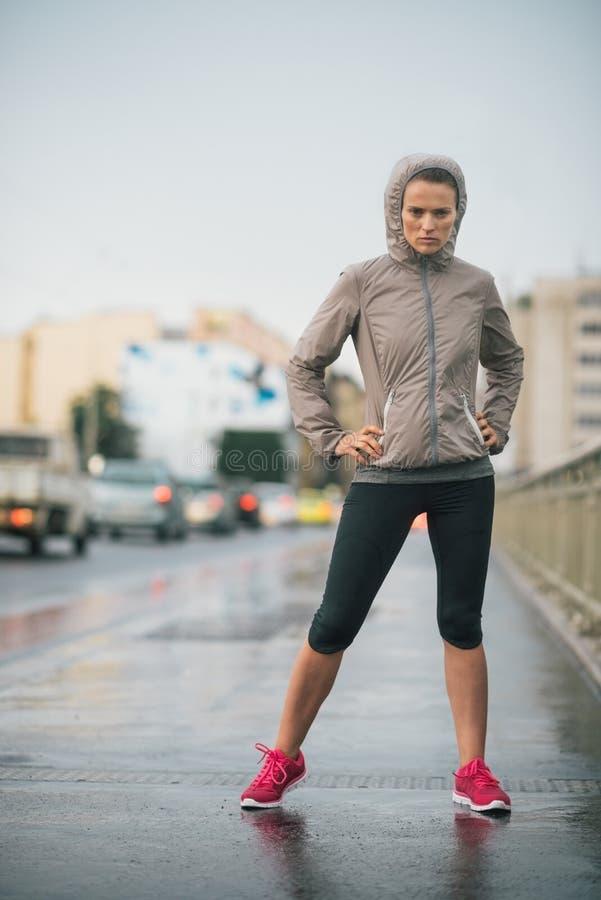 Engrenagem vestindo da chuva do corredor da mulher que sente determinada imagem de stock