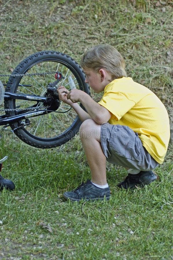 Engrenagens da bicicleta da fixação do menino fotos de stock royalty free
