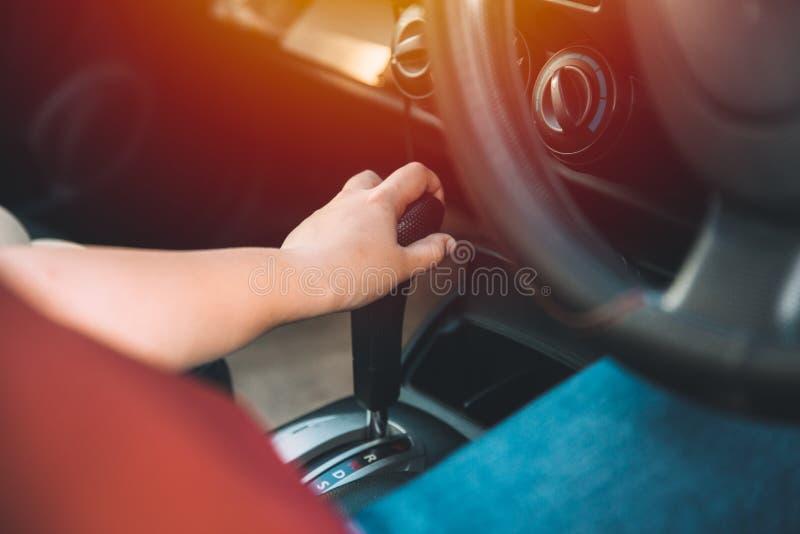 Engrenagens de deslocamento da mão do motorista das mulheres do close up dentro do carro imagens de stock