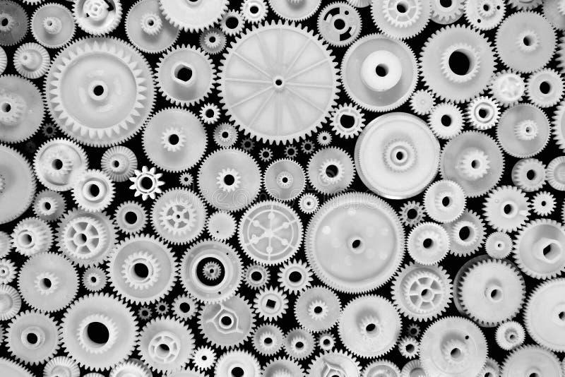 Engrenagens e rodas denteadas plásticas brancas no fundo preto foto de stock