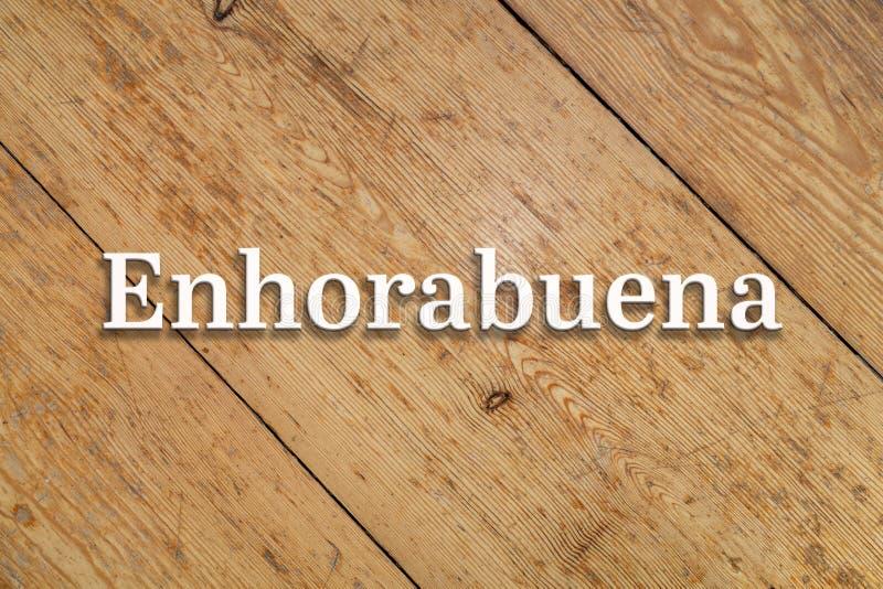 `Enhorabuena` white text on a wooden background. Translation: `Congratulations`. `Enhorabuena` white 3D text on a wooden home background. Translation: ` stock image