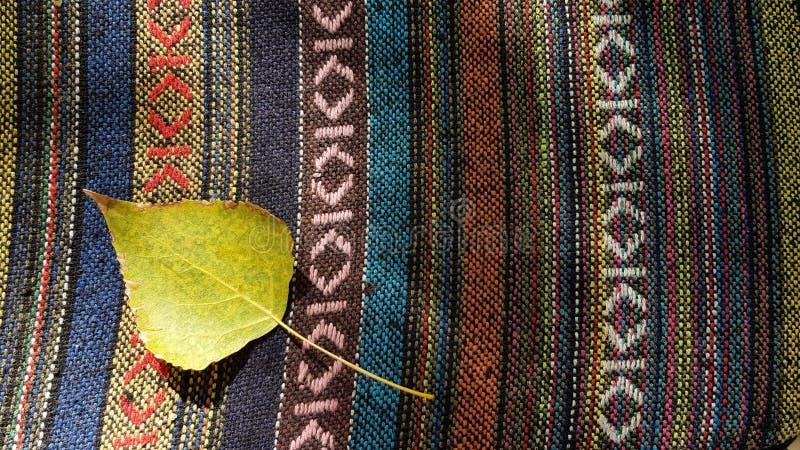 Enig geel blad boven op etnische gestreepte geweven dekenoppervlakte royalty-vrije stock foto