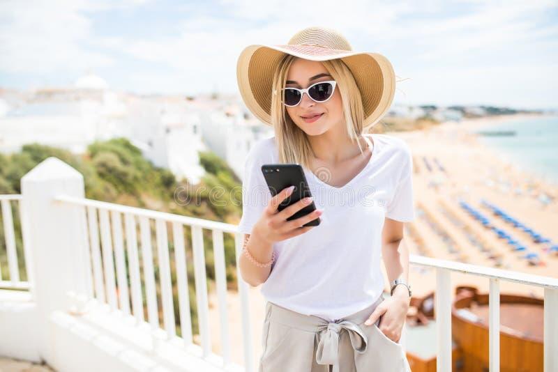 Enig gelukkig meisje die een smartphonezitting in een terras controleren stock foto