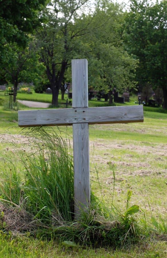 Enig houten kruis in een begraafplaats stock afbeeldingen